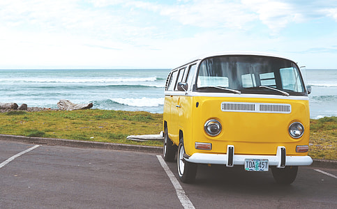 yellow Volkswagen van near body of water