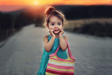 Child with bag at sunset