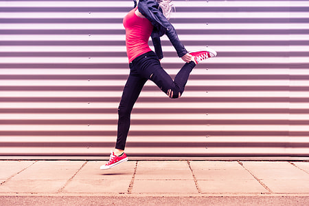Young Happy Woman Jumping in Front of Metal Wall