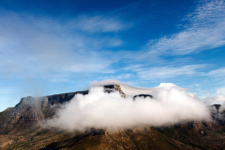 white cloud covering brown rocky mountain during day time