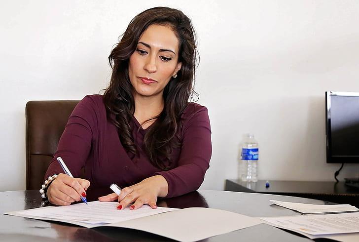 woman wearing maroon dress shirt holding pen