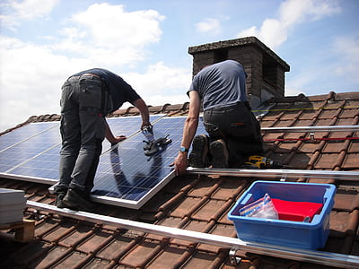 two man putting solar panels on roof