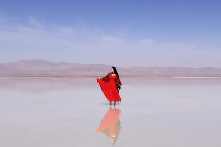 woman in red sari dress on body of water during daytime