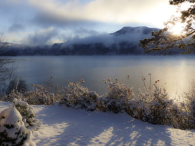 snow covered ground and trees by the river overlooking mountain and sunrise under blue and white cloudy sky