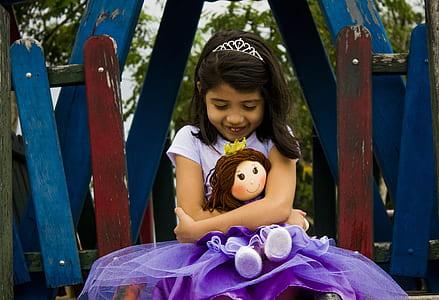 girl in purple t-shirt dress holding rag doll during daytime