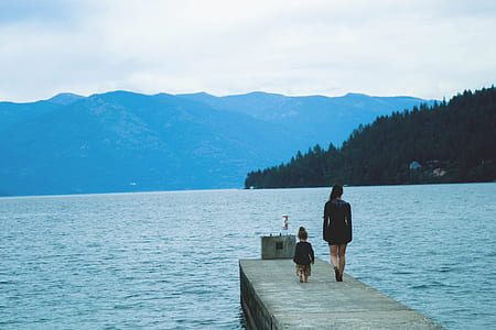woman and child walking on the dock during daytime