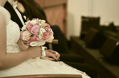 selective focus photography of woman in wedding dress holding bouquet of flowers