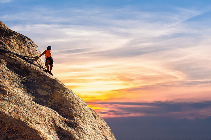 person climbing on rock ledge