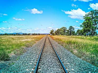 railroad track near green grass field