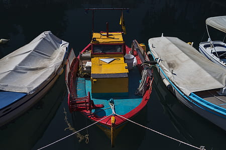 three assorted-color boats on body of water