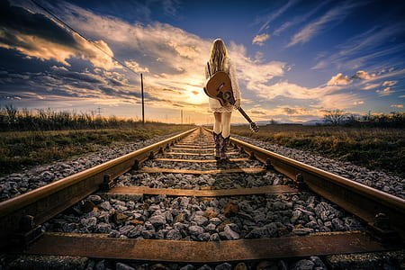 woman carrying acoustic guitar standing on railroad during daytime