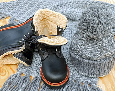 pair of black leather work boots and gray crochet beanie