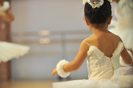 shallow focus photograph of child in white tutu dress