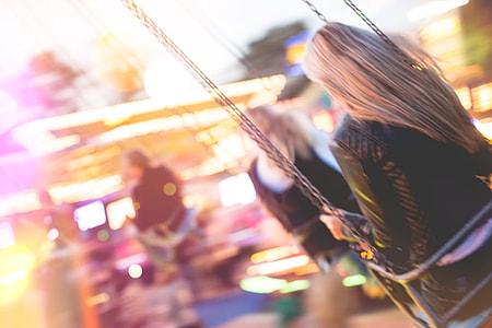 Young Girl Enjoying Crazy Ride on Swing Carousel