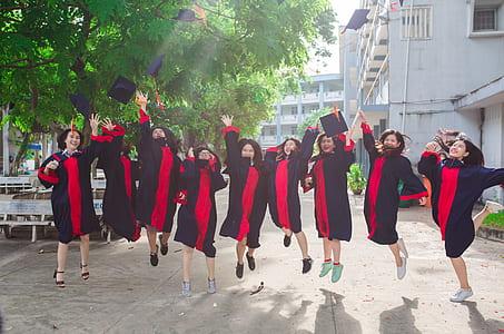 women wearing black and pink academic regalia