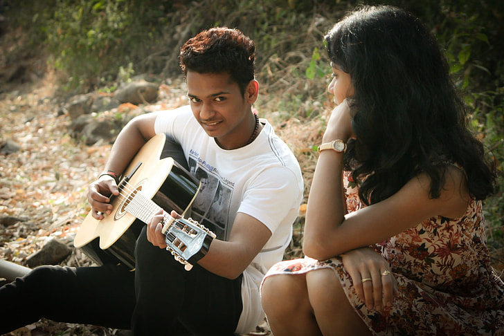 man in white shirt sitting playing guitar with woman beside