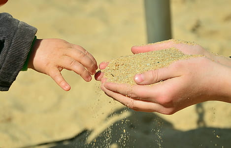 brown sand on person's hand