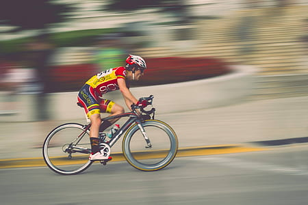 man in yellow and red on bicycle