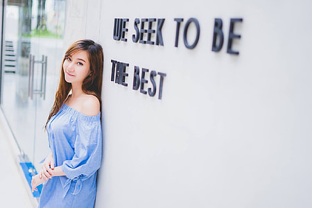 woman in blue off-shoulder dress standing near white concrete wall