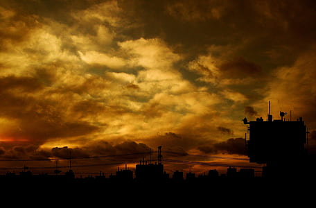 silhouette photo of city under cloudy sky