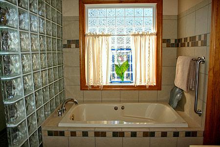 rectangular white enamel bathtub inside room with gray wall tiles