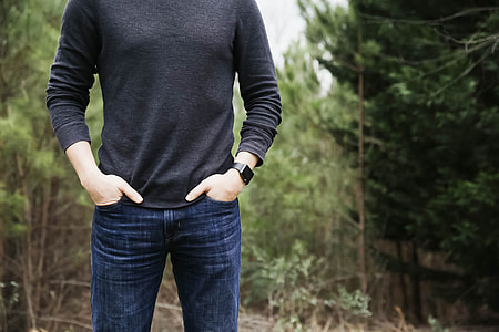 person wearing blue jeans standing on forest