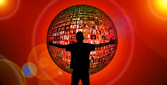 silhouette of man in front of sphere with photo of people