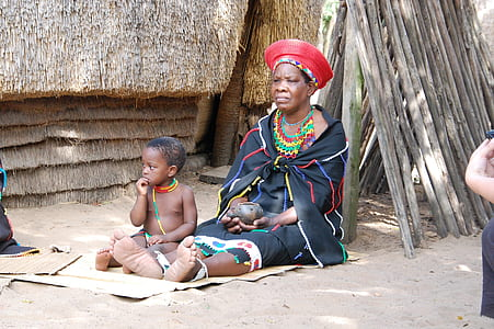 woman in blue, red, blue, and green traditional dress sitting on sand beside baby