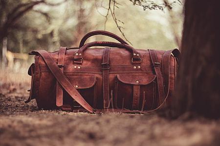 brown leather satchel duffel bag beside brown tree during daytime