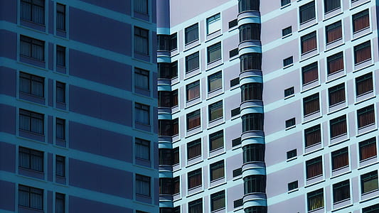 optical illusion photograpy of two blue high-rise buildings