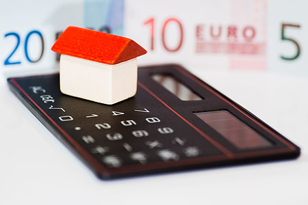 white and red house miniature on top of desk calculator