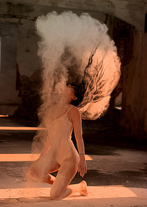 photography of woman in one-piece suit flipping hair with dust