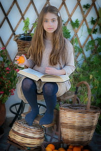 girl in gray knit sweater holding book and orange fruit sitting on chair beside brown wicker basket