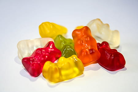 assorted-color gummy bears on white surface