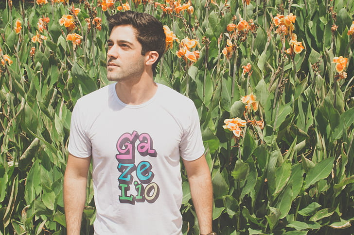 man wearing white and multicolored crew-neck t-shirt beside orange petaled flowers during daytime