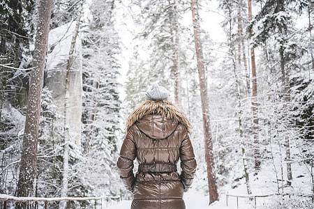 Girl in Winter Jacket Walking in Snowy Forest