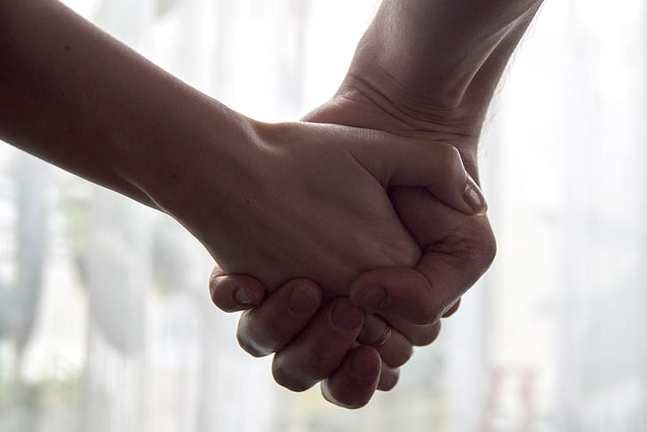 selective focus photography of man and woman holding each other's hands