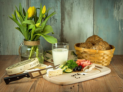 sliced vegetables on chopping board with knife beside glass of milk and basket