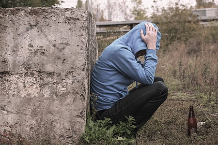 person in blue hoodie leaning on concrete brick