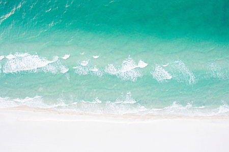 Aerial drone shot of a sandy beach and ocean in the summer