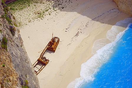 photo of wrecked boat near shore