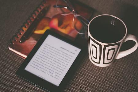 white and black ceramic mug beside black Amazon Kindle ebook reader on gray surface