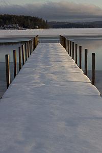 brown wooden bridge with snow