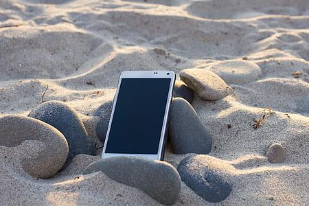 smartphone on black stone and sand