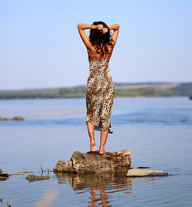 woman standing on brown rock near water during daytime
