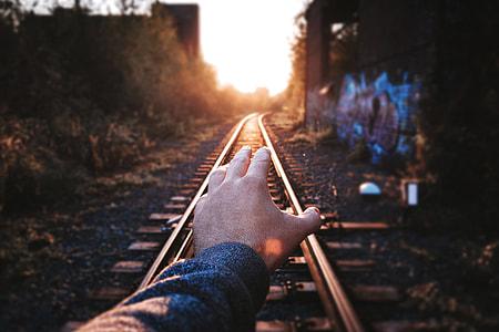 Man's hand on train tracks