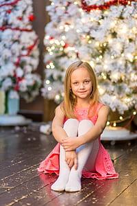 girl in pink sleeveless dress sitting on brown wooden floor