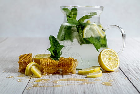 clear glass pitcher with green vegetable and slice lemon