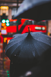 person holding using black umbrella while raining walking outside during daytime