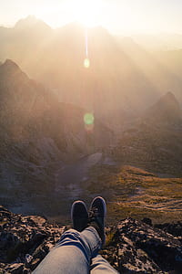 Person Wearing Black Sneakers Sitting in Mountain